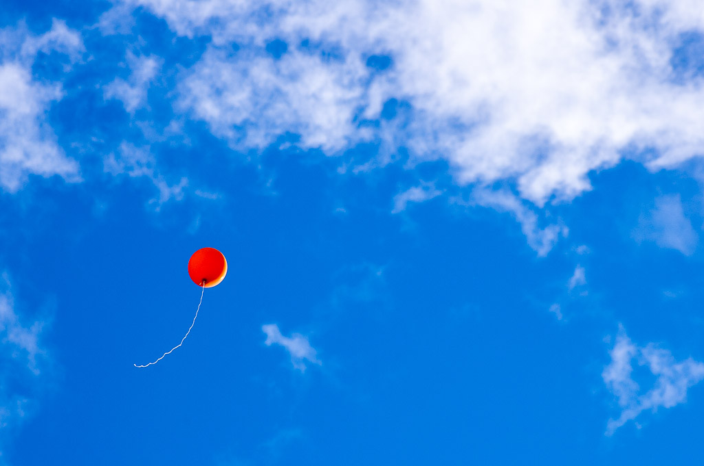 Orange baloon flying away