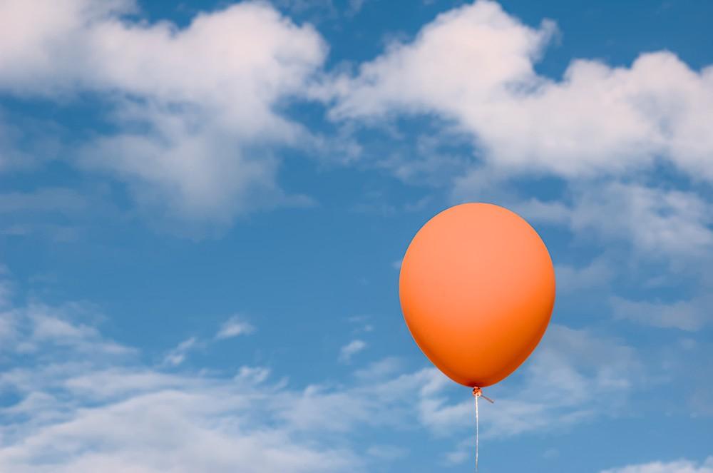 Orange baloon against the sky