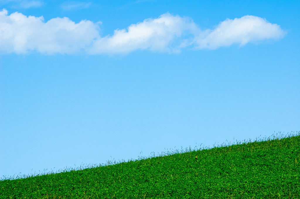 Green slope with clouds