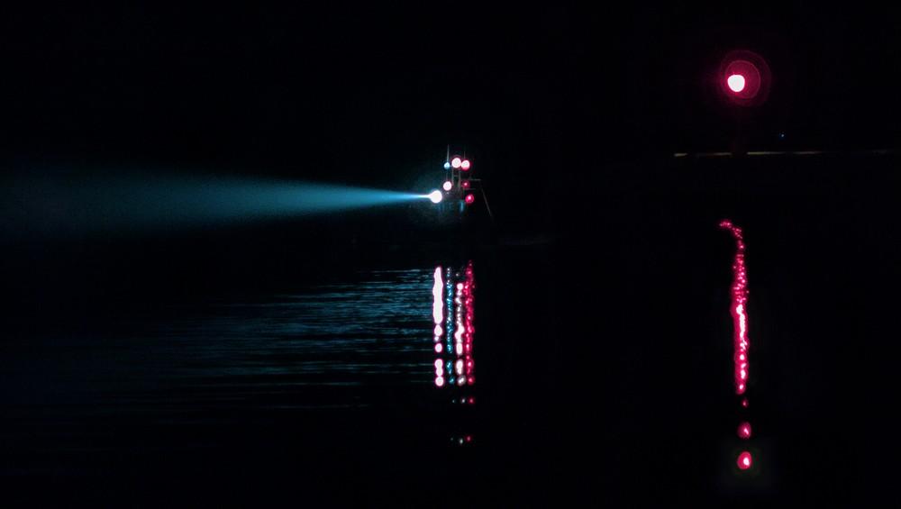 Boat returnig to harbor at night